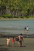 Woman and girls walk on beach at Labilabi, Halmahera, Indonesia.