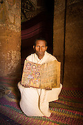 Priest showing ancient text inside Abune Yemata church in the mountains. Near Hawzen Town, Gheralta area, Tigray, Ethiopia, Horn of Africa