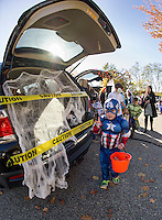 "Chael Smithson ""Captian America"" makes off with a treat from the trunk of Bryan Holland's ""Spiders and Skulls"" mobile during Holy Trinity School's Trunk or Treat on Monday afternoon.  (Karen Bobotas/for the Laconia Daily Sun)"