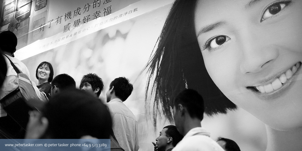 Woman amongst crowd on escalator smiling while exiting a railway station. In the background is a large photograph of another woman smiling.
