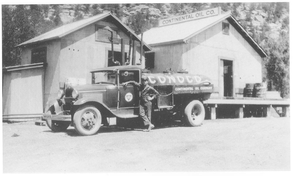"""Conoco truck standing beside Conoco warehouse.<br /> Dolores, CO  1930-1939<br /> In book """"Rocky Mountain Railroads - Vol. 1: The Rio Grande Southern"""" page 74<br /> Also in """"RGS Story Vol. VII"""", p. 123."""