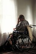 Depressed man in wheelchair looking out window.