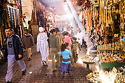 Light beams strike shiny gold arts and crafts on display and for sale at market stalls along a crowded pedestrian street in the Marrakech medina, Morocco.