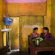 Teenager girls in a colorful restaurant. Hand washing station in the corner.