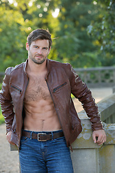 shirtless man in a leather jacket outdoors
