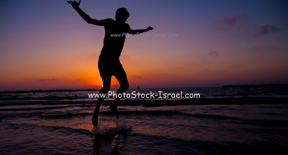 Silhouette of a youth playing on the Beach at sunset