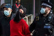 Kent Police officers arrest one of two Palestine Action activists who occupied an area above the entrance to Discovery Park House which had been sprayed with red paint in protest against the presence in Discovery Park of an Instro Precision factory on 4th October 2021 in Sandwich, United Kingdom. Instro Precision is a subsidiary of Israels largest publicly-traded arms company Elbit Systems supplying high precision military equipment and Palestine Action contends that Instro Precision equipment has been used by the Israeli military against the population of Gaza.