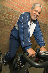 Older man on his exercise bike at his home gym,