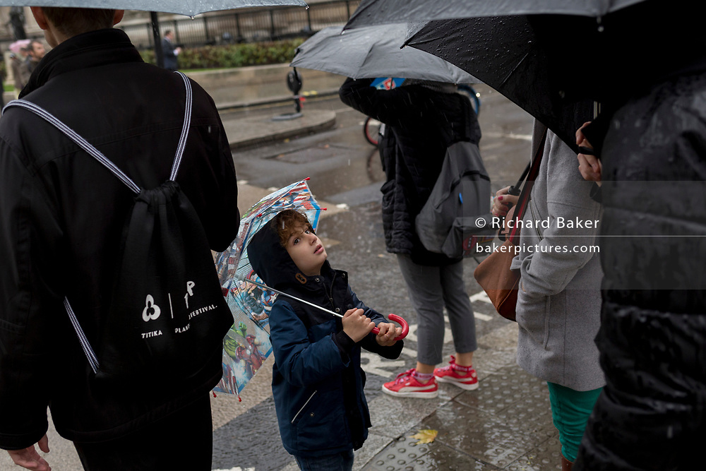 A young visitor to the capital endures heavy rainfall on an autumn afternoon outside St. Martin-in-the-Fields church on Trafalgar Square, on 24th October 2019, in Westminster, London, England.