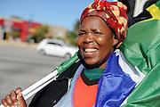 Vrouw zwaait met de Zuid Afrikaanse rainbow nation vlag op een kruispunt in Port Elizabeth.