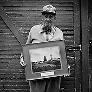 """The late John """"Jack"""" Murnaghan, a retired union organizer holding a retirement gift which is a photo of the Macassa Mine where he worked for 43 years.  At the time this photograph was taken, Murnaghan was living alone and suffering from Alzheimer?s disease, Kirkland Lake, Ontario.  From the book Cage Call: Life and Death in the Hard Rock Mining Belt. An in-depth project spanning over 12-years examining communities in one of the richest mining regions in the world located in Northwestern Ontario and Northeastern Quebec in Canada."""