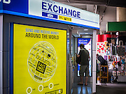 08 JULY 2015 - BANGKOK, THAILAND:   People walk past an exchange booth in Bangkok while foreign visitors to Thailand buy Baht Wednesday. Thai financial markets and the Thai Baht both lost value Wednesday. The stock market, the Stock Exchange of  Thailand (SET) closed at 1,470.25, down 13.52 or 0.91%, from Tuesday. The Thai Baht closed at 33.90 Baht to 1 US Dollar, it's lowest point since September 2009. Economists blamed the drop in the Chinese stock markets and uncertainty over the EU's handling of the Greek budget crisis for the drops in Thai markets.  PHOTO BY JACK KURTZ
