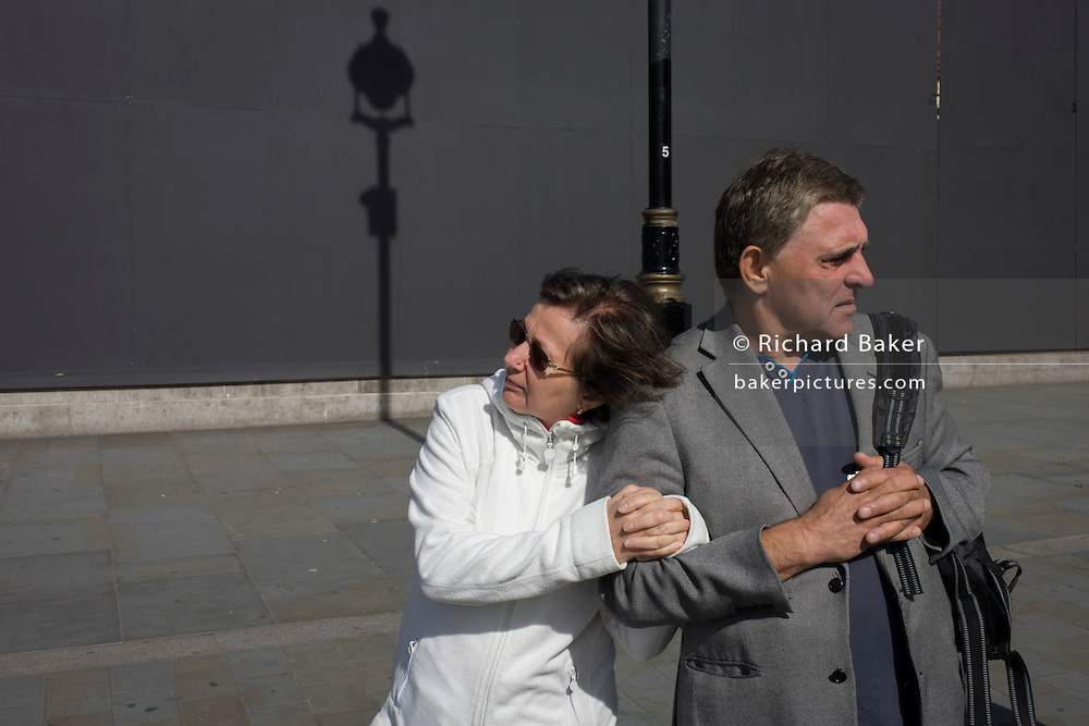 Couple arm in arm with a lamp post shadow against a grey construction hoarding in central London's Trafalgar Square.