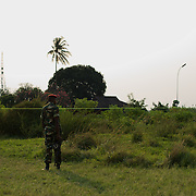 A soldier from the Burundian National Army takes guard to the perimeter of a football field used as a polling station in Musaga neighbourhood, Bujumbura, June 29, 2015.