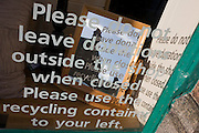Charity shop request not to leave items outside store are repeated in a mirror and on a wall.