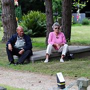 NLD/Amsterdam/20070823 - Begrafenis Jos Brink, 2 mensen zittend op een graf