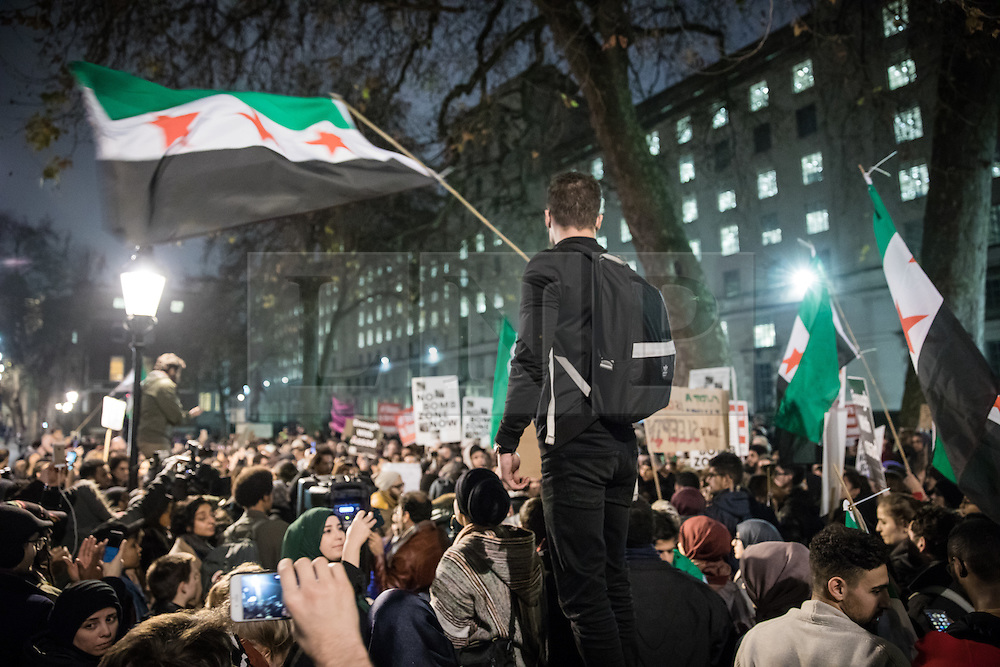 © Licensed to London News Pictures. 13/12/2016. London, UK. People gather opposite Downing Street, London, to protest the bombardment of the Syrian city of Aleppo and call for an immediate ceasefire to allow the evacuation of civilians and the delivery of humanitarian aid. Syrian government forces, supported by Russian and Iranian air strikes, are attempting to retake the rebel-held eastern districts of the city, containing tens of thousands of civilians. Photo credit: Rob Pinney/LNP