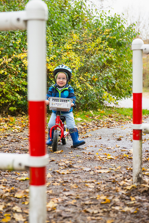 Little boy driving a walking bicycle through barrier