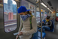 Passenger Andrew Brandi, 22, looks at his phone while riding the Metrorail wearing a protective mask and gloves during the COVID19 pandemic in Miami on Wednesday, April 1, 2020.
