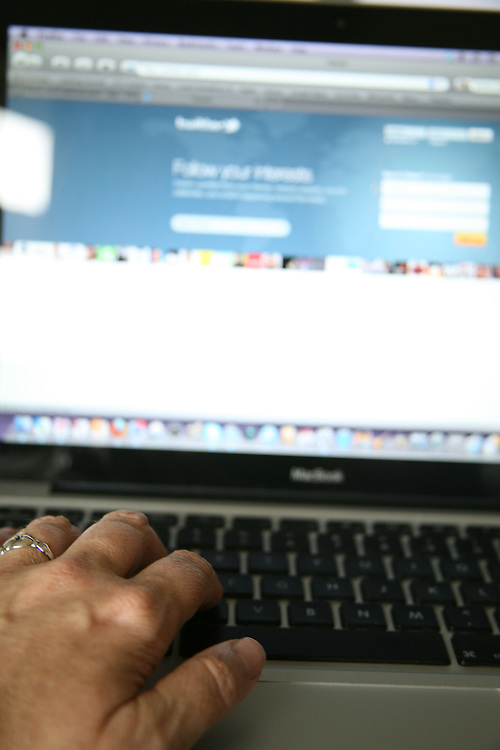 Close-up of a person using twitter on a laptop