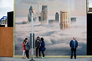 Tourists await a bus beneath a property developer's billboard showing a large aerial image of London skyscrapers in low cloud on Shoreditch High Street showing a large aerial image of London skyscrapers in low cloud. This site will be called Principal Place, a new 15-storey office block designed by Foster and Partners in Worship Street, Shoreditch, London. The mural image shows some of the capital's best-known tall buildings that rise above the fog - now a very unusual weather phenomenon after thick fogs in the 1950s.