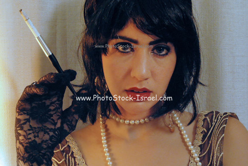 Sensual 1920s vintage style woman smokes a cigarette with holder