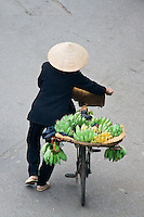 Baskets of yellow and green bananas are wheeled around town on the back of street vendors bicycles,
