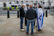 """London, United Kingdom, May 11, 2021: A pro-Israeli protestor carrying an Israeli Flag is seen gathered outside Downing Street nearby the pro-Palestinian demonstrators who are gathered to protest against Israeli atrocities in London on Tuesday, May 11, 2021. Chanting """"FREE! FREE Palestine!"""" demonstrators are demanding the commitment of Great Britain to end their support for Israel. They are strongly opposing Israeli planned evictions of Palestinian families in the Sheikh Jarrah neighbourhood of East Jerusalem. This is the second week of ongoing protests to be held across England. (Photo/ Vudi Xhymshiti)"""