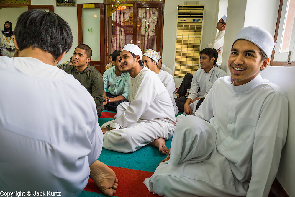 """08 AUGUST 2013 - BANGKOK, THAILAND: Men in the prayer room at Haroon Mosque in Bangkok on Eid al-Fitr. Eid al-Fitr is the """"festival of breaking of the fast,"""" it's also called the Lesser Eid. It's an important religious holiday celebrated by Muslims worldwide that marks the end of Ramadan, the Islamic holy month of fasting. The religious Eid is a single day and Muslims are not permitted to fast that day. The holiday celebrates the conclusion of the 29 or 30 days of dawn-to-sunset fasting during the entire month of Ramadan. This is a day when Muslims around the world show a common goal of unity. The date for the start of any lunar Hijri month varies based on the observation of new moon by local religious authorities, so the exact day of celebration varies by locality.      PHOTO BY JACK KURTZ"""
