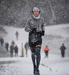 © Licensed to London News Pictures. 24/01/2021. London, UK. A man jogging in heavy Snowfall on Hampstead Heath in Hampstead in north London. Parts of the UK continue to suffer from flooding caused by Storm Christoph. Photo credit: Ben Cawthra/LNP