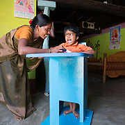 CAPTION: Aishwarya's legs are so weak, she cannot stand without support. She also goes through long periods of constant crying. During the earliest days following the birth of a child who has (or develops) a disability or special needs, parents often struggle to work out what they can do for him or her, and could use more information and firmer direction. Under the Chamkol programme, such children aged between zero and five and their mothers, expectant mothers and women of child-bearing age will be able to get this through health, wellbeing, development and pre-school programmes run through Early Years' Clubs. LOCATION: Mallianpura (village), Kasaba (hobli), Chamrajnagar (district), Karnataka (state), India. INDIVIDUAL(S) PHOTOGRAPHED: Nagamma H.S. (left) and Aishwarya (right).