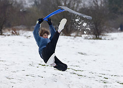 © Licensed to London News Pictures. 24/01/2021. Epsom, UK. A youth using a snow scooter gets airborne in the snowy conditions on Epsom Downs in Surrey. A band of snow is crossing the south east this morning as temperature remain just above freezing. Photo credit: Peter Macdiarmid/LNP