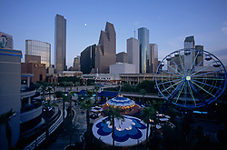Skyline of Houston, Texas at dusk featuring the Downtown Aquarium ferris wheel in the foreground.