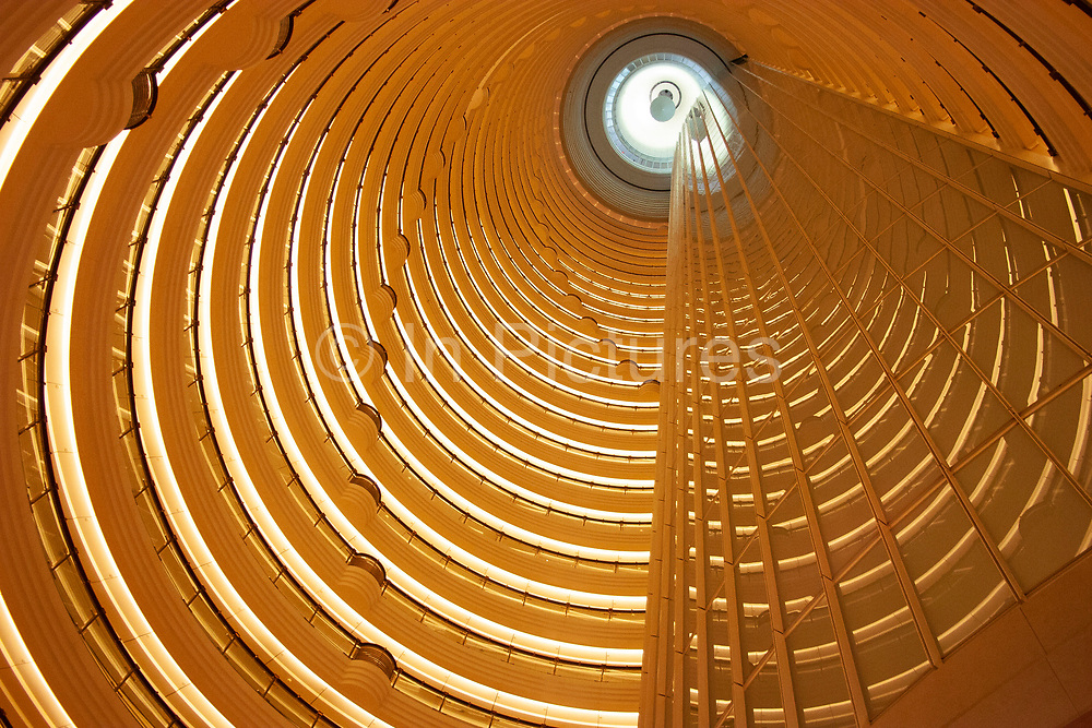 Atrium of the Grand Hyatt hotel inside the Jin Mao Building, Pudong in Shanghai, China. This view taken from the 55th floor of the Jin Mao Building looks at the top section of this amazing tower which is owned by the Hyatt hotel group. Looking up, the top floor in this view shows the 85th floor balcony. This interior has become famous as one of Shanghais tourist attractions, with many people paying to see the view from the viewing deck on the 87th floor. The symmetry and repetition of floors and balconies is breathtaking and visually overloading at the same time.