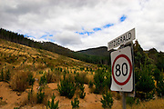 80km speed limit signs entering Fitzgerald, near Maydena, Tasmania. In the background is a clearcut replanted with plantation forest by Forestry Tasmania.