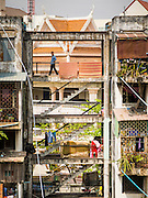 24 FEBRUARY 2015 - PHNOM PENH, CAMBODIA: People on a staircase of the White Building in Phnom Penh. The White Building, the first modern apartment building in Phnom Penh, originally had 468 apartments, and was opened the early 1960s. The project was overseen by Vann Molyvann, the first Cambodian architect educated in France. The building was abandoned during the Khmer Rouge occupation. After the Khmer Rouge were expelled from Phnom Penh in 1979, artists and dancers moved into the White Building. Now about 2,500 people, mostly urban and working poor, live in the building. Ownership of the building is in dispute. No single entity owns the building, some units are owned by their occupants, others units are owned by companies who lease out apartments. Many of the original apartments have been subdivided since the building opened and serve as homes to two or three families. The building has not been renovated since the early 1970s and is in disrepair. Phnom Penh officials have tried to evict the tenants and demolish the building but residents refuse to move out.   PHOTO BY JACK KURTZ