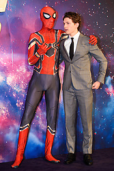 Tom Holland (right) poses with a Marvel cosplayer attending the Avengers: Infinity War UK Fan Event held at Television Studios in White City, London.