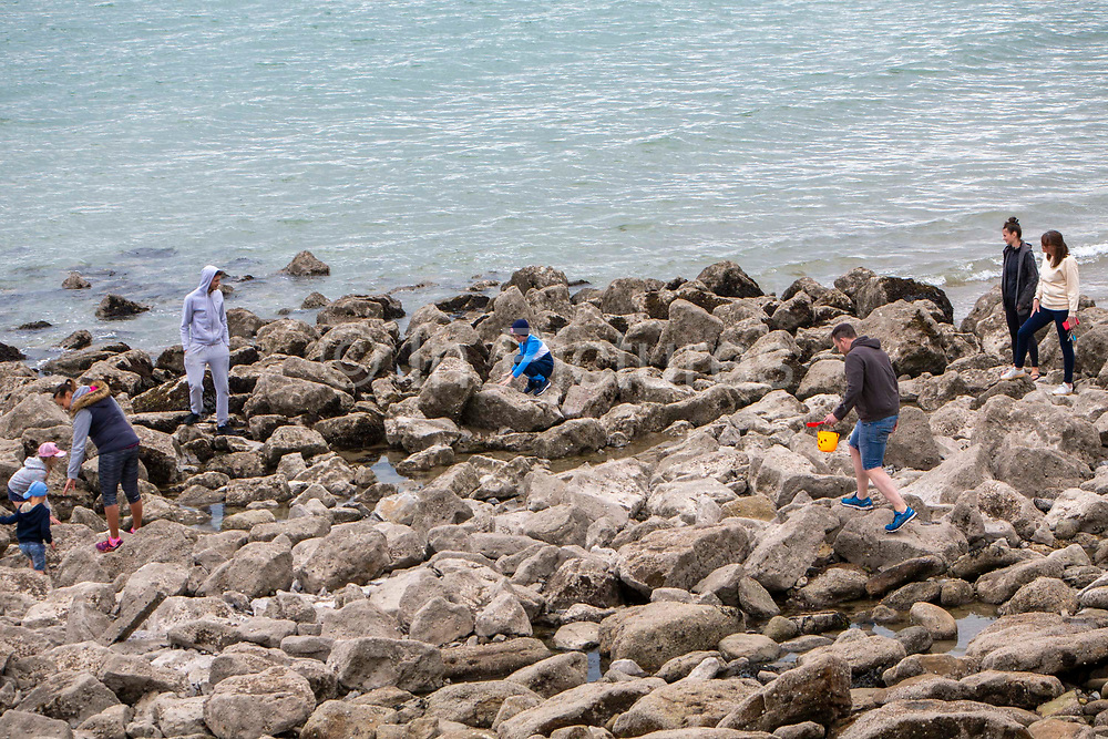 Residents of Folkestone rock-pooling at a safe distance in the rocky area of Sunny Sands beach on the 16th of May 2020 in Folkestone, United Kingdom. Rock pooling is a common past time for families visiting the seaside.