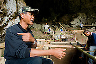 Researcher Wahyu Saptomo coordinates logistcs above an excavation pit at Liang Bua cave, discovery site of the Flores hobbit, Homo floresiensis
