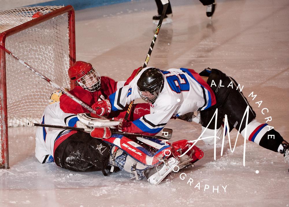 MAILer's Garret Dunlap crashes Laconia's Tom Missert into MAILer goalie C.J. Tsantoulis during Wednesday's clash at the Laconia Ice Arena.  (Alan MacRae/for the Citizen)