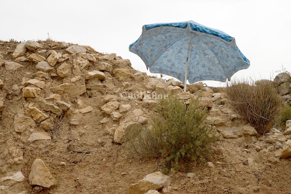 an umbrella sticking out above a rocky hill