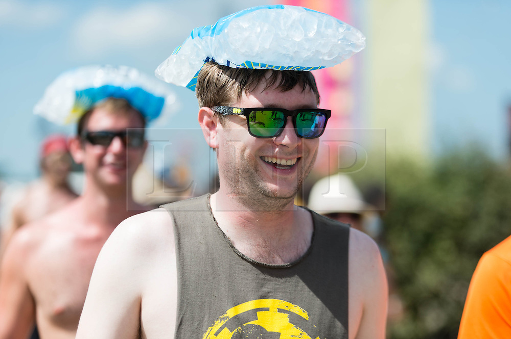 © Licensed to London News Pictures. 13/06/2014. Isle of Wight, UK.  Festival goers carry bags of ice on their heads to cool themselves from the hot morning sun at the Isle of Wight Festival 2014.   Today is expected to be the hottest day of the year.  The Isle of Wight festival is an annual music festival that takes place on the Isle of Wight. Photo credit : Richard Isaac/LNP
