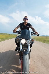 American Motordrome Wall of Death rider Cyclone Jake Wheeler takes the back roads north of Sturgis to the Broken Spoke County Line during the Sturgis Black Hills Motorcycle Rally. SD, USA. August 4, 2014.  Photography ©2014 Michael Lichter.