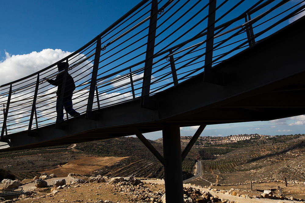 The West Bank Jewish settlement of Eli is seen in the background as a silhouetted Israeli child is seen visiting the archaeological park of Ancient Shiloh, which is located at the entrance to the modern Jewish settlement of Shiloh, south of the Palestinian West Bank town of Nablus, on January 1, 2017. Shiloh was the religious capital of Israel, an assembly place for the people of Israel and a center of worship before the first temple was built in Jerusalem. Its sacred area housed the Ark of Covenant.