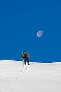 A climber ascends a snow covered slope leading to the moon below Snow King Mountain, Glacier Peak Wilderness, Washington.