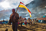 A man holds a flag for identify to the people from his village between thousands of pilgrims in the valley during the celebration of the Lord of Qoyllur Rit'i (The Lord of the Shining Snow), in Cusco, Peru.