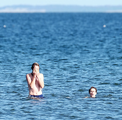 Kayne and Tamsin from the Republic of Ireland in the sea at Portobello Beach in Edinburgh during a sunny first day of Autumn.<br /> <br /> Edinburgh Weather Pictures, Thursday 22nd September 2016<br /> <br /> (c) Alex Todd | Edinburgh Elite media