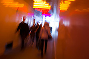 Blurred pedestrians walk through a multi-coloured tunnel under a large construction site in Knightsbridge, on 11th April 2019, in London England.