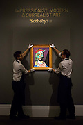 Two members of staff hold Femme Au Beret Et a La Robe Quadrillee - Marie-Therese Walter by Pablo Picasso, on February 22nd, 2018 at the preview for Sothebys upcoming Impressionist, Modern and Surrealist Art auction at Sothebys in New Bond Street, London, England.
