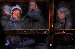 KABUL,AFGHANISTAN - SEPT. 10:   Afghan  widowed women make dough inside a screened room at a bakery set up to help vulnerable families in Kabul, Afghanistan September 10,2002. (Photo by Ami Vitale/Getty Images)